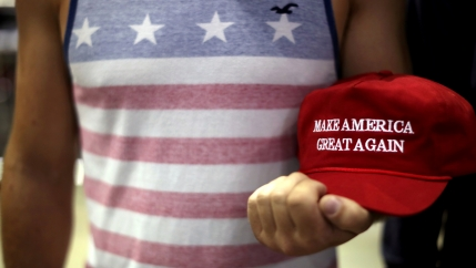 Person holds red MAGA hat in his hand.
