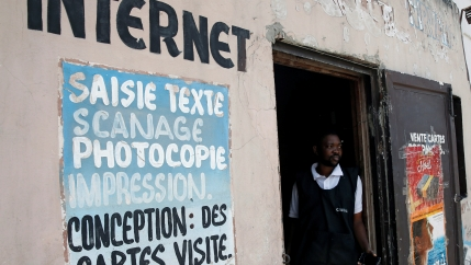 Man stands at entrance to internet cafe.