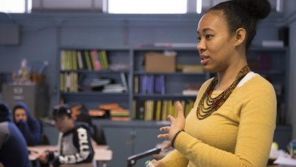 A teacher speaks in front of the classroom.