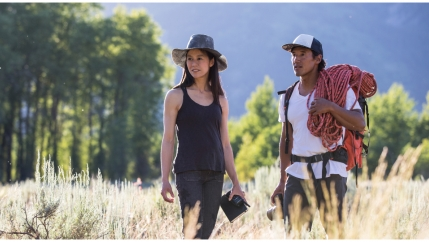 A man carrying a climbing rope stands on a field with a woman wearing a black hat.