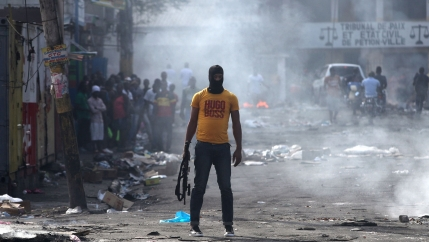 A man is shown holding a weapon, wearing a yellow Hugo Boss t-shirt, next to burning barricades.