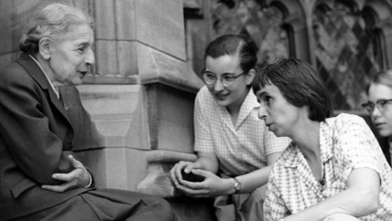 An elderly white woman sits on a step, talking with two younger white women.