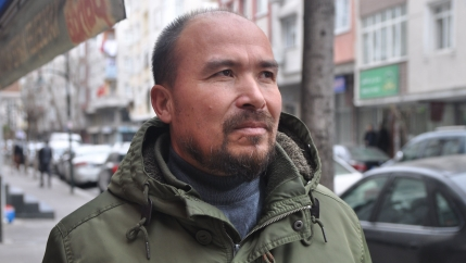 Photo of a bald Uighur man wearing an army-green jacket.