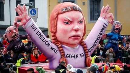 A parade float in the image of Greta Thunberg holds two politicians by the ears
