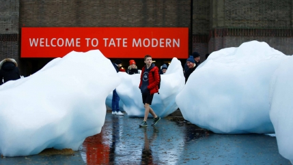 A person stolls between large pieces of ice in front of the Tate Modern in London