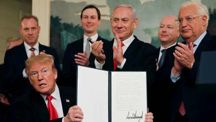Donald Trump sits and holds up a signed proclamation while flanked by Israeli Prime Minister Benjamin Netanyahu and Jared Kushner