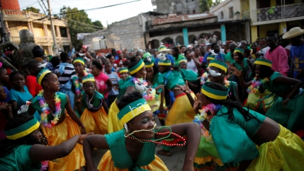 Women in green and yellow costumes dance