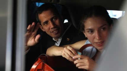 Venezuelan opposition leader Juan Guaidó sits in the back seat of a car next to his wife Fabiana Rosales waving.