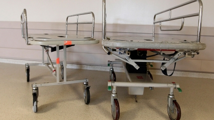 A smaller metal gurney is shown next to a larger one in the hallway of a maternity ward at the University of Alabama Hospital.