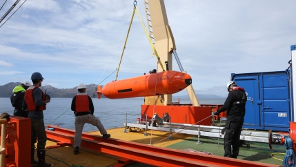 Researchers hoist the orange-colored Hugin autonomous submarine onto the deck of the Nathaniel B. Palmer.