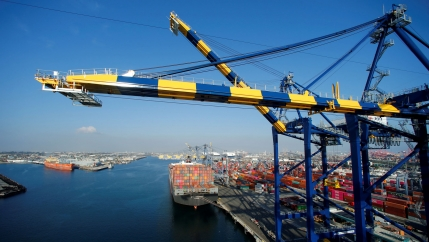A ship is show loaded with thousands of containers with a blue and yellow crane in the nearground.