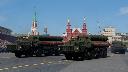 Three large 8-wheeled trucks carrying air defense systems are shown driving down a street.