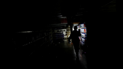 A darkened supermarket is show with one lone flashlight being used by a worker.