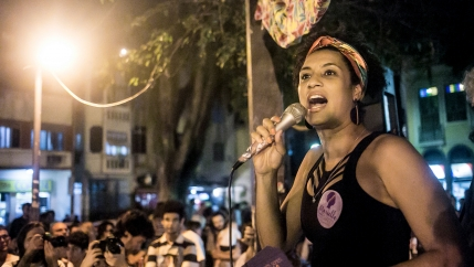Marielle Franco speaks on a mic