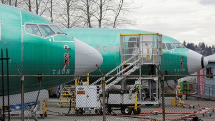 The front end of two Boeing 737 MAX 8 aircraft with a green body and white nose, are parked at a Boeing production facility.