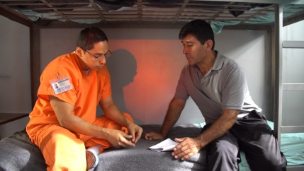 Two men sit on a prison bunk bed, one wearing an orange jumpsuit and the other in plain grey clothes.