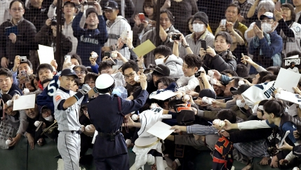 Seattle Mariners' outfielder Ichiro Suzuki gives autographs to fans before an exhbition game in Tokyo against the Yomiuri Giants, March 17, 2019.