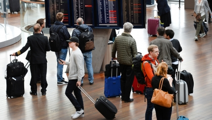 Travelers with roller bags walk and look at departure screens