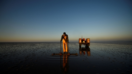 A man in overalls is shown looking down at the sea bed on his cockling board.