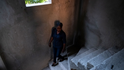 A woman is shown walking down a cement staircase in Port-au-Prince, Haiti.