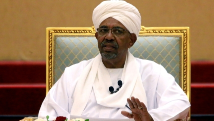 Omar al-Bashir is shown wearing all white while sitting in a chair with his left hand raised slightly.