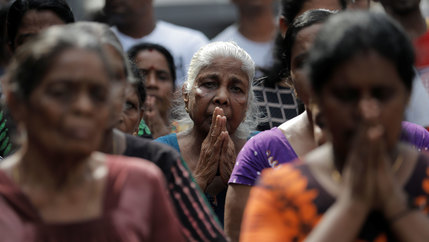 A crowd of older women are shown with their hands folded in prayer