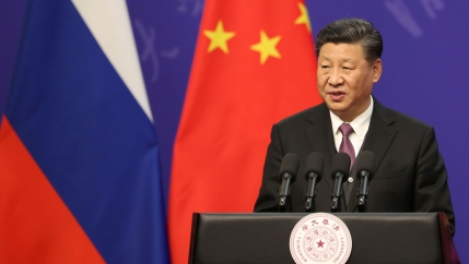 Chinese President Xi Jinping is shown standing at a podium with four microphones.