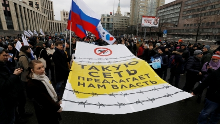 Protesters wa;l through the streets of a city carrying Russian flags and large signs written in Russian.