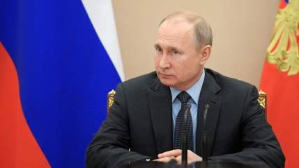 Vladimir Putin sits at a desk with the Russian flag behind him.