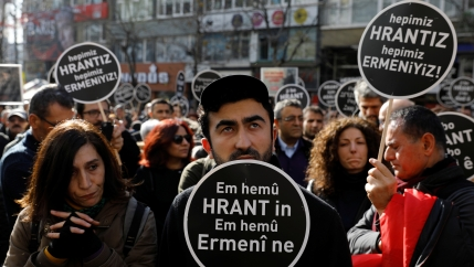 Protesters carry black sign with white writing in support of slain Armenian journalist.