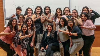 A group of Latina women in front of white boards pose for the camera