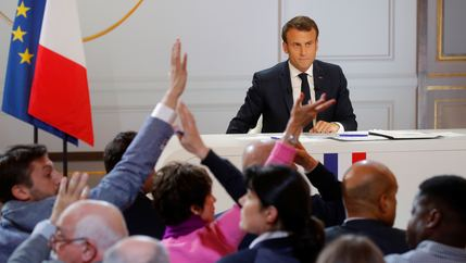 Macron is at the front of a room and hands of journalists are in the air