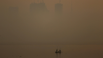 a fishing boat in front of a very smoggy mumbai