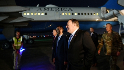 US Secretary of State Mike Pompeo is shown wearing a dark suit and blue tie while walking on the tarmac in Iraq with a State Dept. airplane in the background.