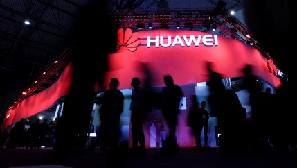 Several people in shadow are shown walking by a red illuminated sign for Huawei.