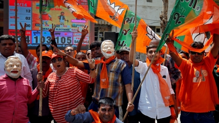 Several people are shown with Indian Prime Minister Narendra Modi masks on and carrying flags.