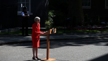 British Prime Minister Theresa May is shown standing at a wooden podium and wearing a red suit.