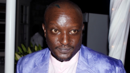 Portrait of the late Binyavanga Wainaina in shiny purple suit with white shirt