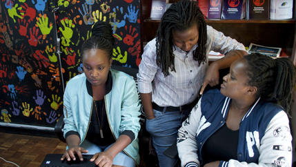 Three women sit around a laptop with background of colorful handprints