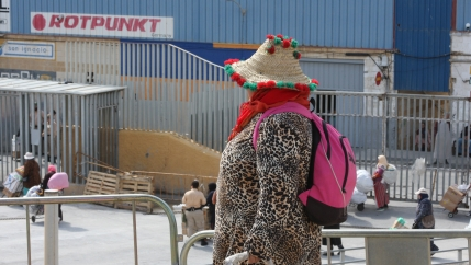 A woman porter in Ceuta wears colorful straw hat and leopard print jacket