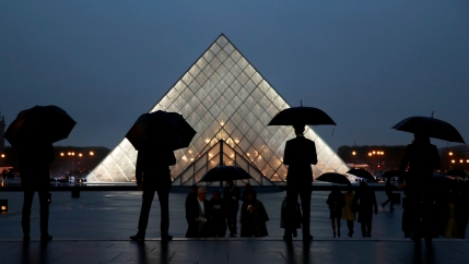 Silhouetted people with umbrellas stand in front of the Louvre pyramid at night.