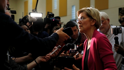Elizabeth Warren stands in front of camera and microphones.