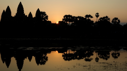 Angkor Wat is shown by a pond at sunrise.