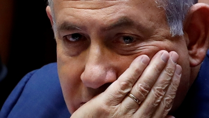 Benjamin Netanyahu sits with his hand covering his mouth.