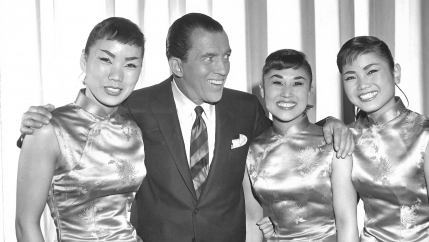 black and white photo of three women and a man standing on stage
