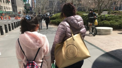 A girl and a woman carry bags and have their back turned to the camera on a city street