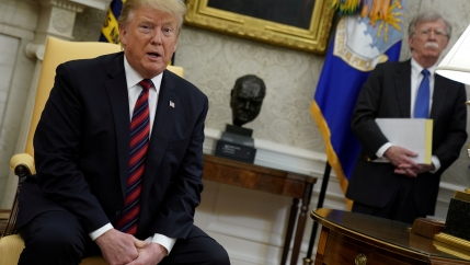 US President Donald Trump speaks to reporters with National Security Adviser John Bolton looking on in the Oval Office at the White House