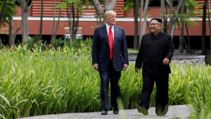 US President Donald Trump and North Korea's leader Kim Jong Un walk together before their working lunch during their summit at the Capella Hotel on the resort island of Sentosa, Singapore.