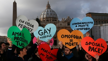 Several people are shown standing in St. Peter's square and holding heart-shaped signs.