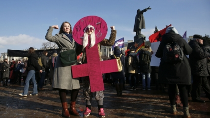 Two women hold their arms in a bicep flex pose. One is wearing a pink cardboard costume in the shape of the women's gender sign.